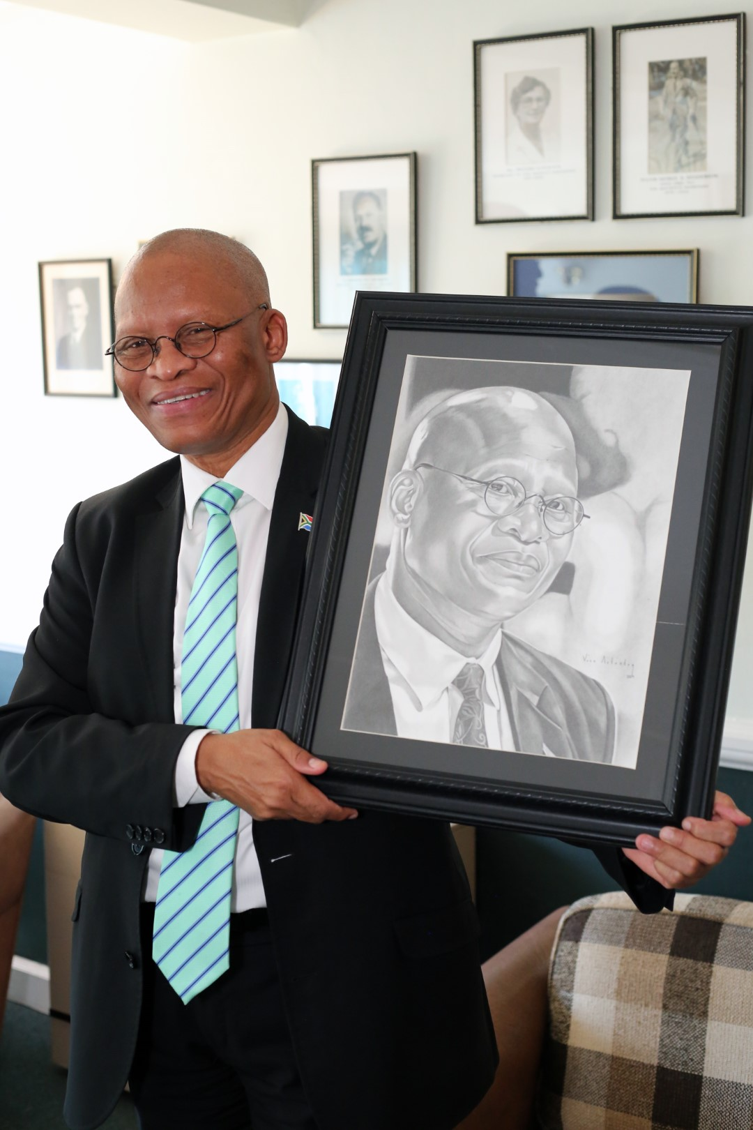 Chancellor Chief Justice Mogoeng Mogoeng is thrilled to recieve a framed sketching of himself