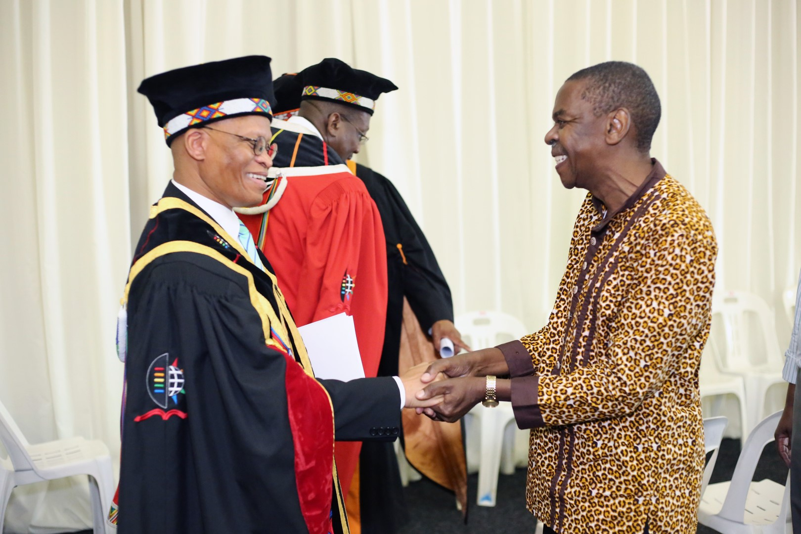Chancellor Chief Justice Mogoeng Mogoeng shares a light hearted greeting with Protas Madlada